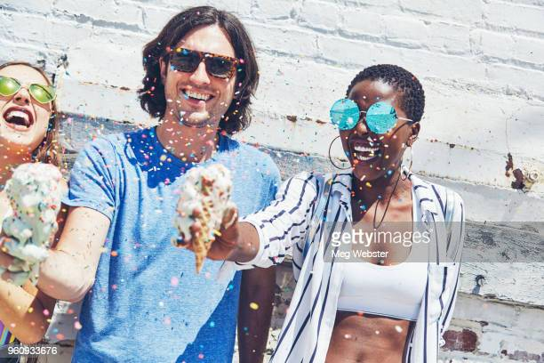 Young man and women holding melting ice cream cones, showering in sugar strands