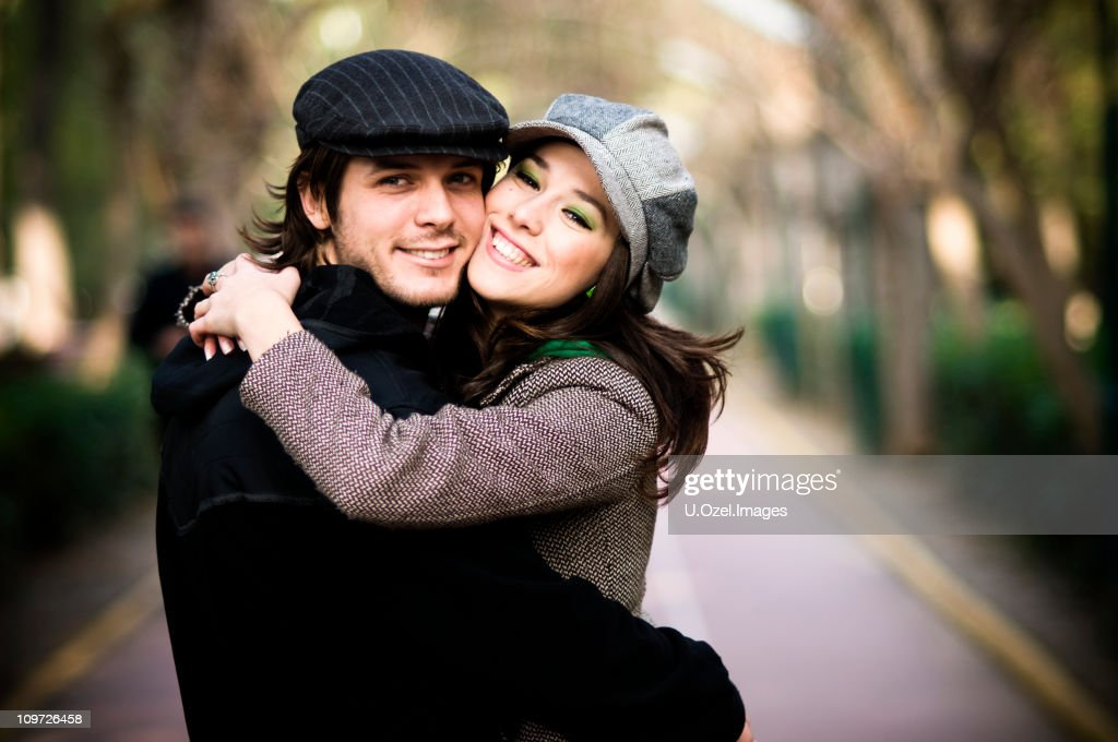 A young man and women hugging each other affectionately : Stock Photo