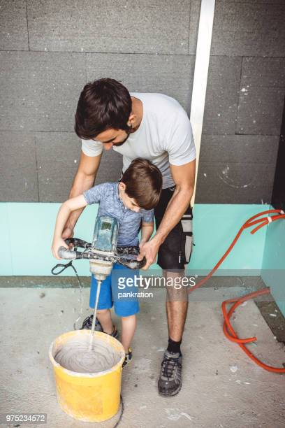 young man and young boy together mixing cement for house wall - foundation make up stock pictures, royalty-free photos & images