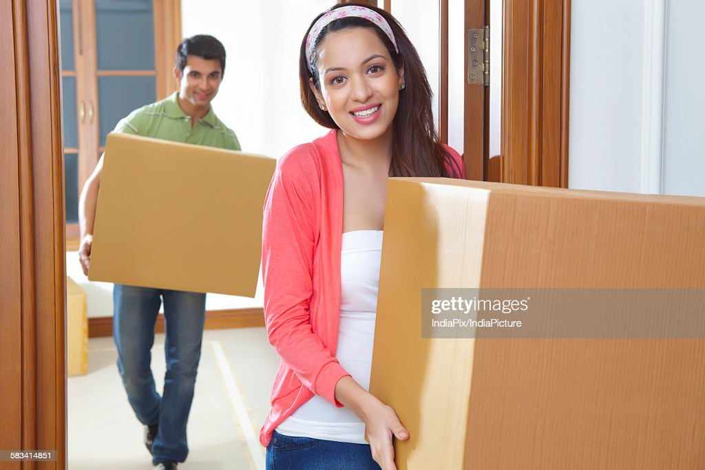 Young man and young woman carrying cartons : Stock Photo
