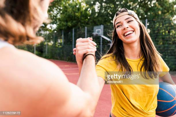 young man and young woman high-fiving after basketball game - sports stock-fotos und bilder