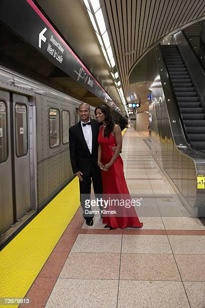 Young man and young woman in subway platform, wearing evening clothes