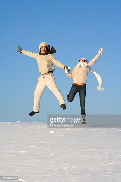 Young man and young woman jumping over a snowy landscape