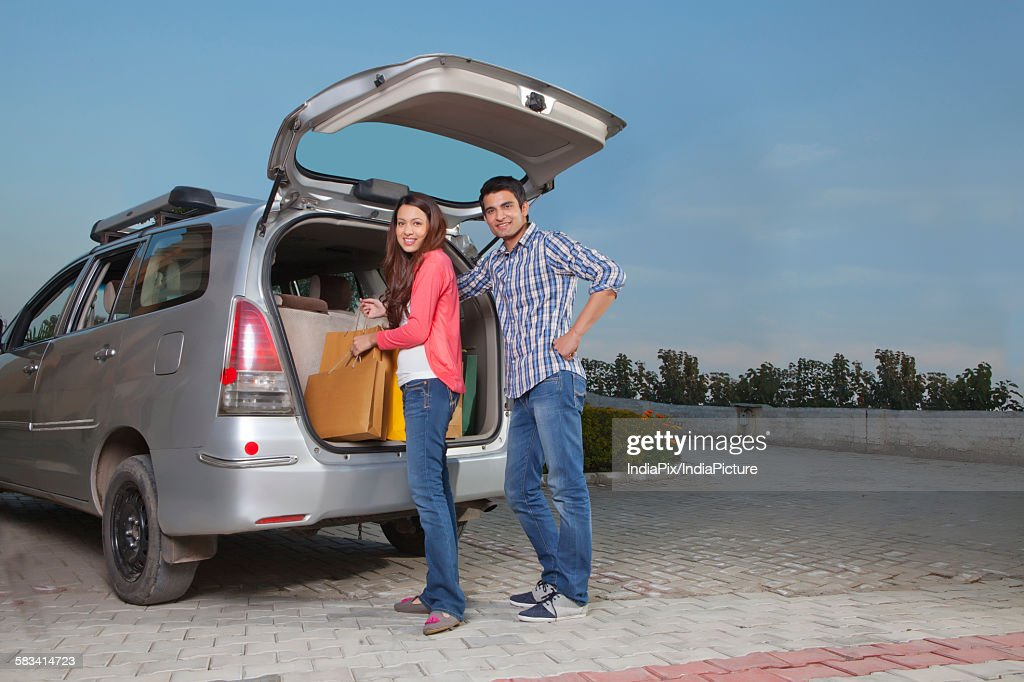 Young man and young woman keeping bags in trunk of car : Stock Photo