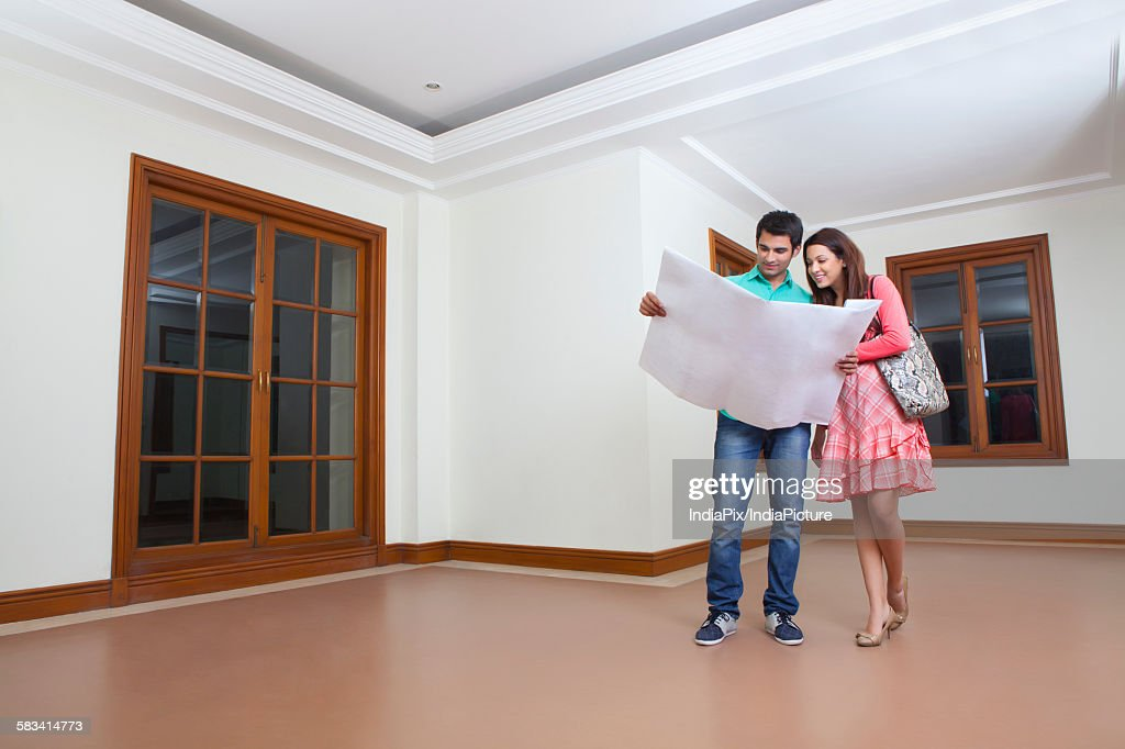 Young man and young woman looking at lay out of house : Stock Photo