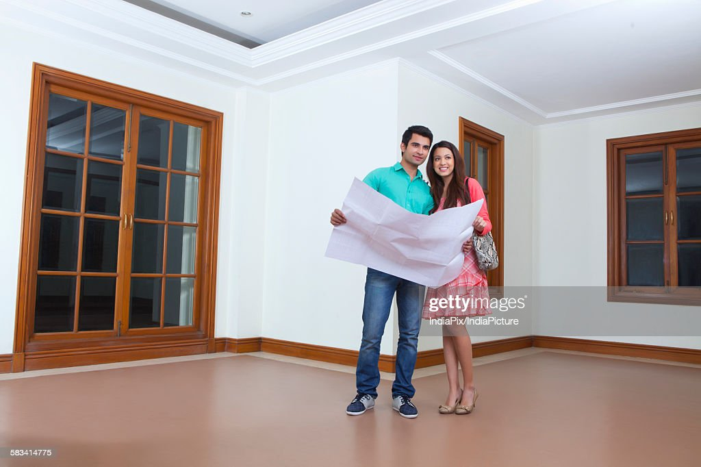 Young man and young woman looking at lay out of houseYoung man and young woman looking at lay out of house : Stock Photo