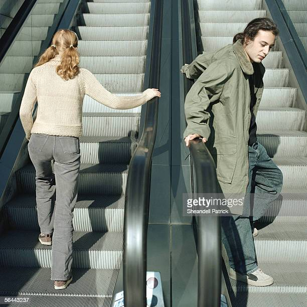 young man and young woman on escalators - stranger stock pictures, royalty-free photos & images