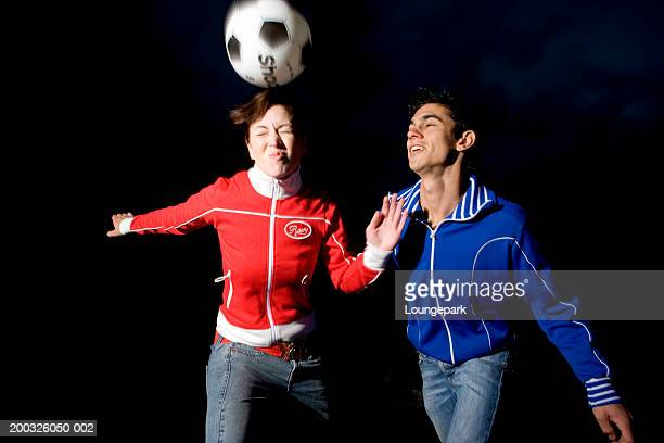 young man and young woman playing football, blurred motion - trainingsoberteil stock-fotos und bilder