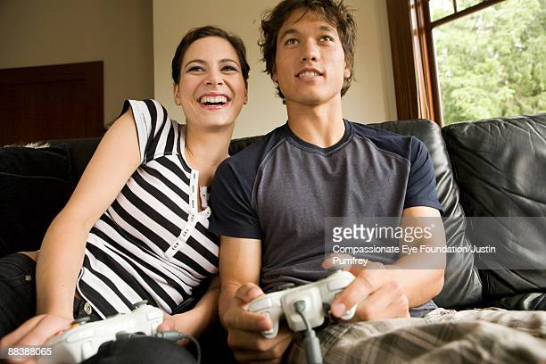 "young man and young woman playing video game - ""compassionate eye"" fotografías e imágenes de stock"