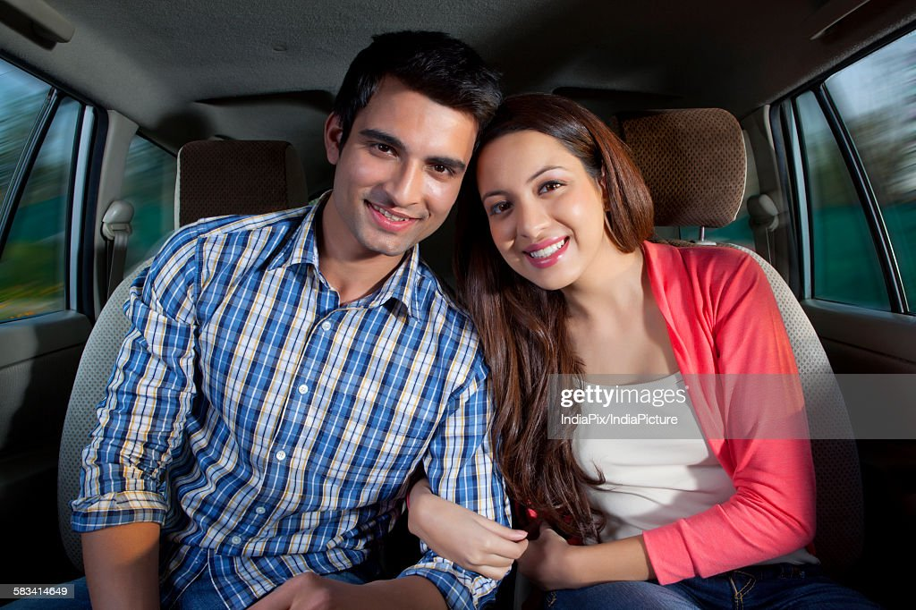 Young man and young woman sitting in a car : Stock Photo