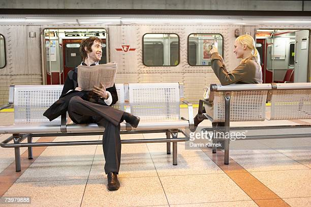 young man and young woman sitting in subway platform, smiling - u bahnzug stock-fotos und bilder