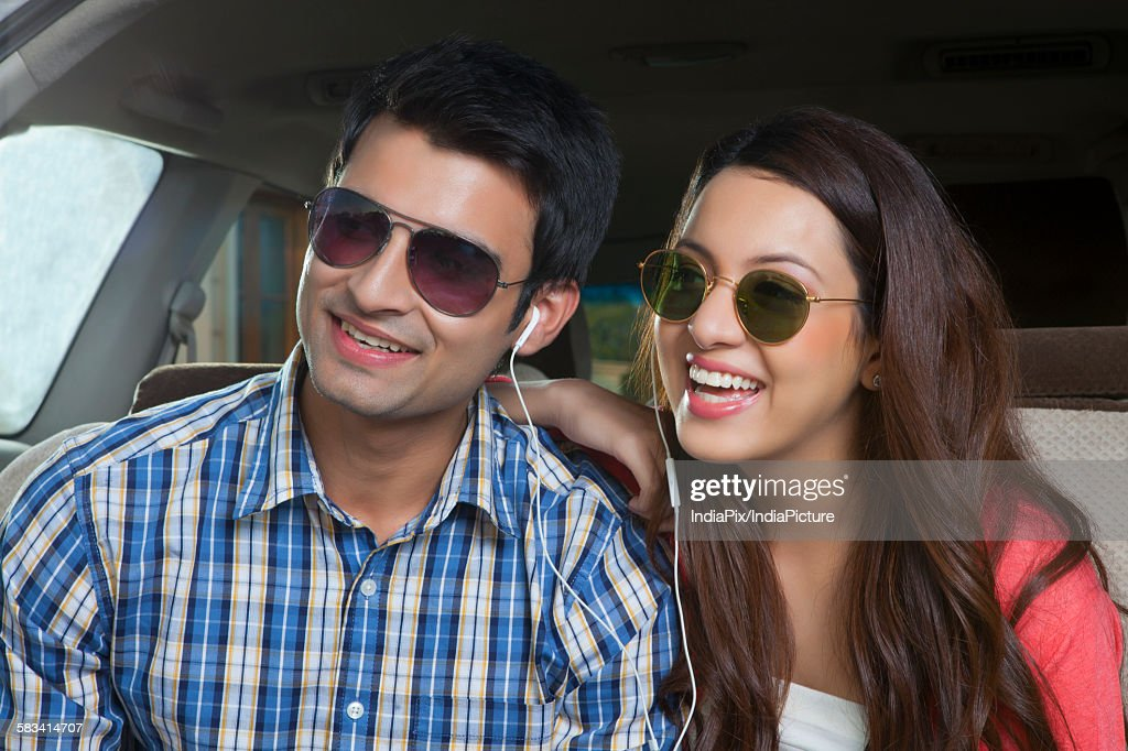 Young man and young woman sitting in the trunk of a car : Stock Photo