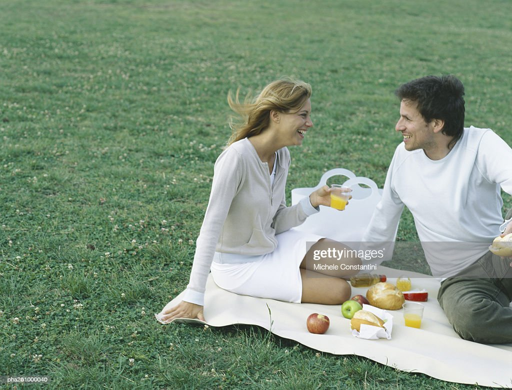 Young man and young woman sitting on blanket on grass having picnic : Stockfoto