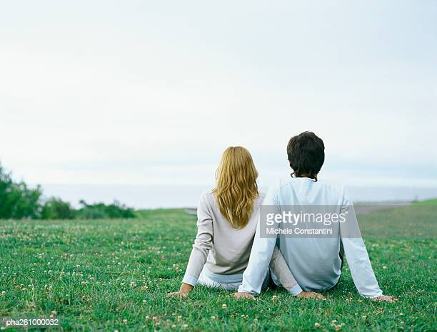 Young man and young woman sitting side by side on grass, propped up with hands, rear view