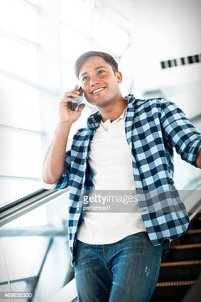 Young man answering mobile phone