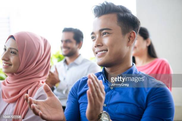 young man applauding in business conference - awards ceremony stock pictures, royalty-free photos & images