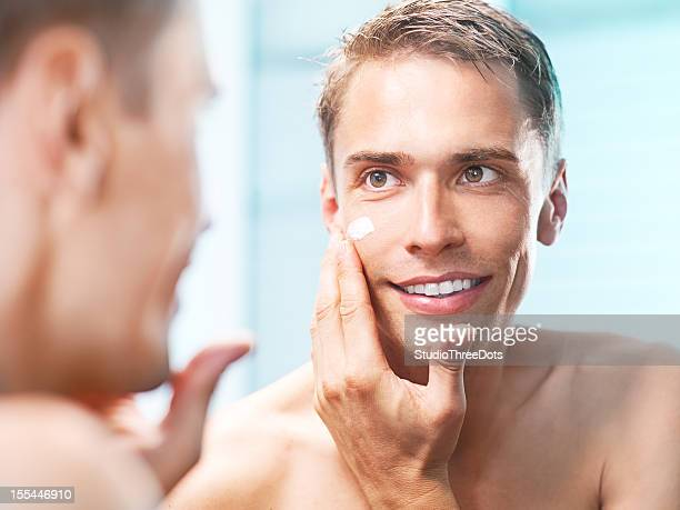 young man applying a face cream front of the mirror