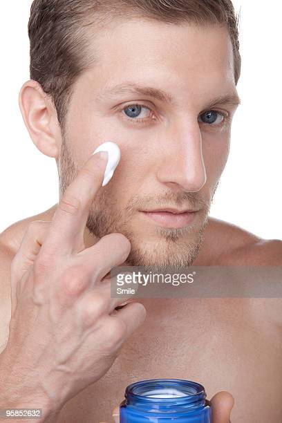 Young man applying cream on face