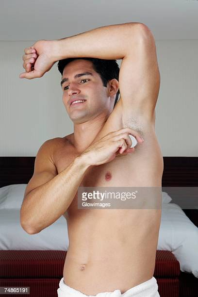 Young man applying deodorant under his armpit