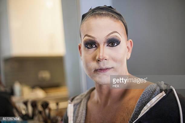 Young man applying drag makeup