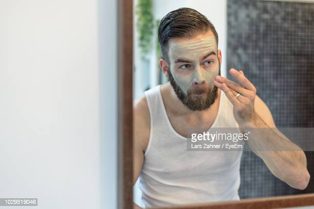 young man applying facial cream while looking into mirror at home - body care stock pictures, royalty-free photos & images