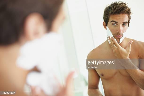 Junger Mann anwenden Rasierschaum ins Gesicht