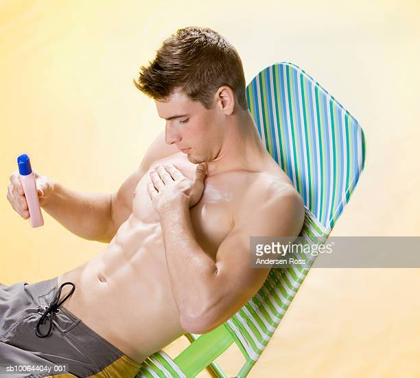 Young man applying sunscreen, sitting on lounge chair in studio, elevated view