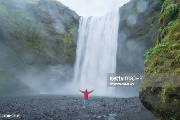 Young man arms outstretched at spectacular waterfall in Iceland