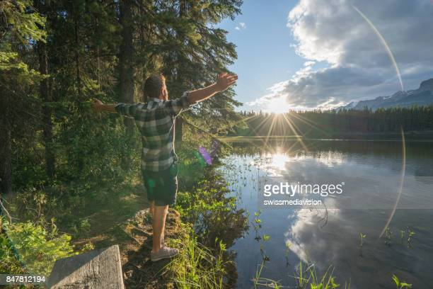 Young man arms outstretched by the lake at sunrise