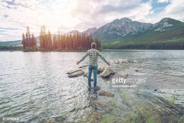 Young man arms outstretched in nature, Canada