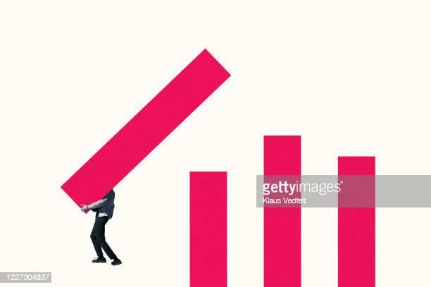 young man arranging pink bar graph - バイアス ストックフォトと画像