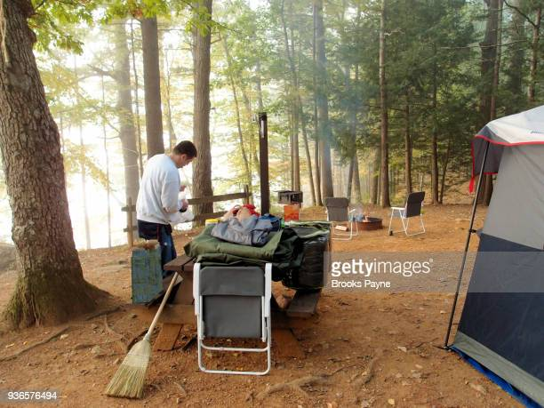 young man arranging supplies at campground. - sturbridge stock photos and pictures
