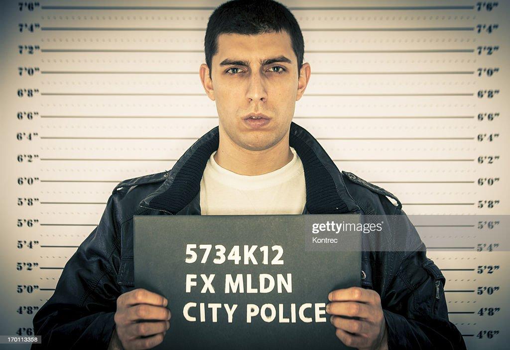 Young man detenidos frente a una prisión tabla de medida : Foto de stock