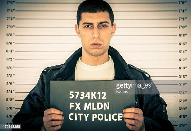 young man arrested in front of a jail height chart - police mugshot stock pictures, royalty-free photos & images