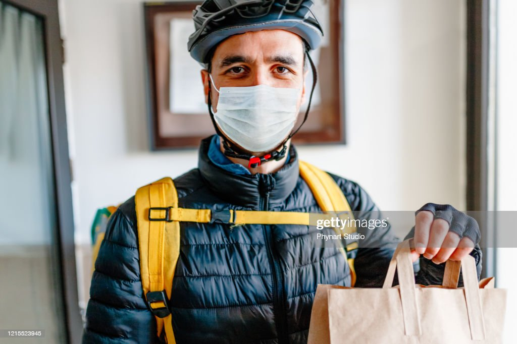 Young man as a courier delivering  food : Stock Photo