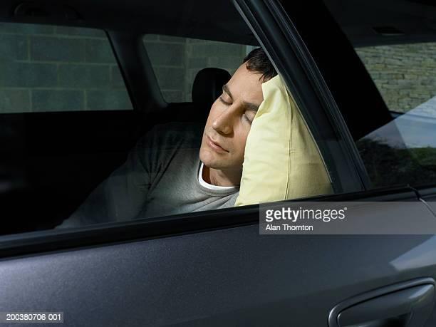 Young man asleep in car, view through window