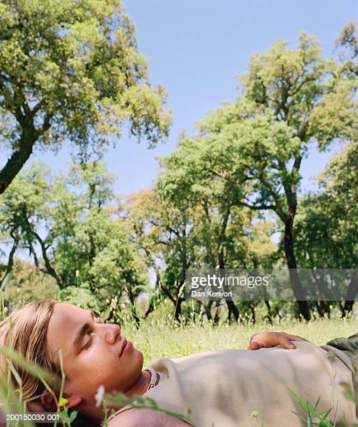 Young man asleep in woodlands, close-up