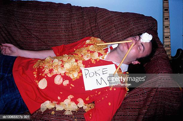 young man asleep on sofa covered in crisps wearing sign - drunk stock pictures, royalty-free photos & images