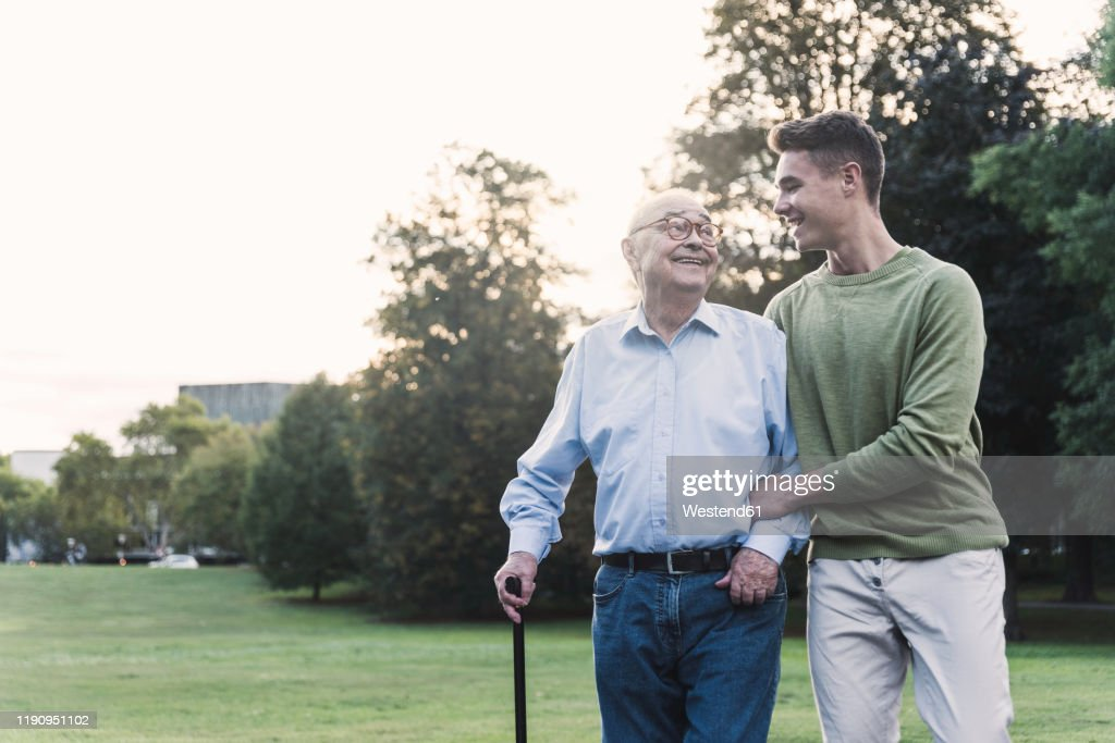 Young man assisting his grandfather walking in a park : Stock Photo