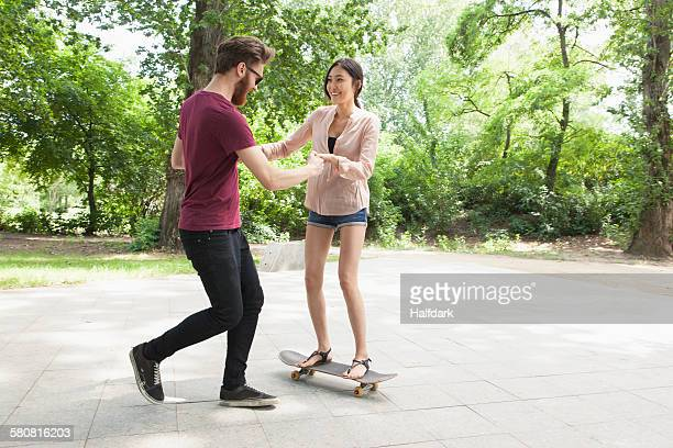 Young man assisting woman in skateboarding on footpath at park
