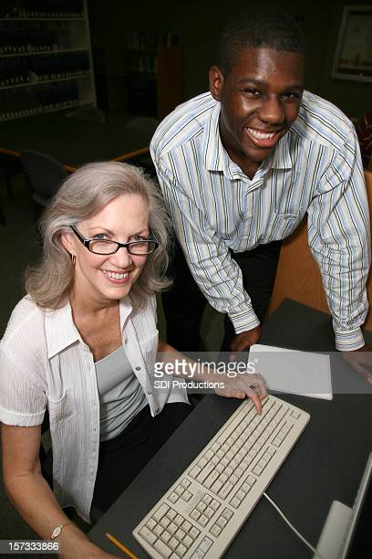 young man assisting woman on a computer - teacher bending over stock photos and pictures