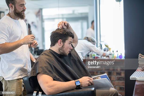 Young man at barbers shop discussing with hairdresser