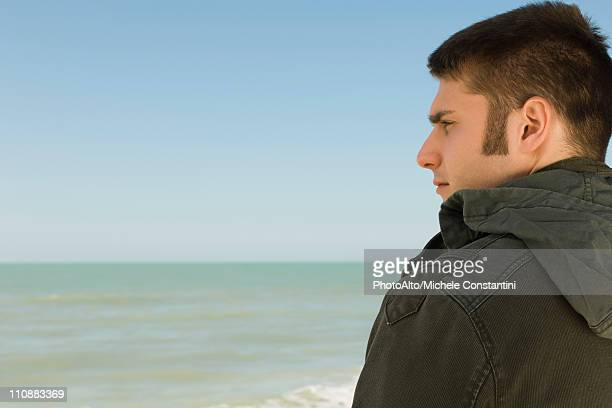 young man at beach contemplatively looking at view - sideburn stock pictures, royalty-free photos & images
