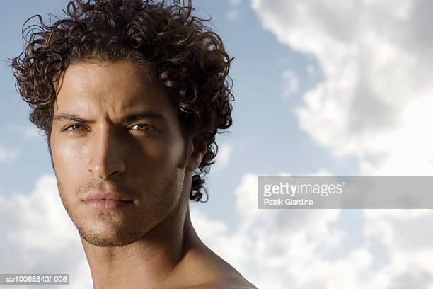 Young man at beach, portrait, close-up