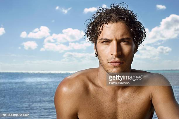 Young man at beach, smiling, portrait, close-up