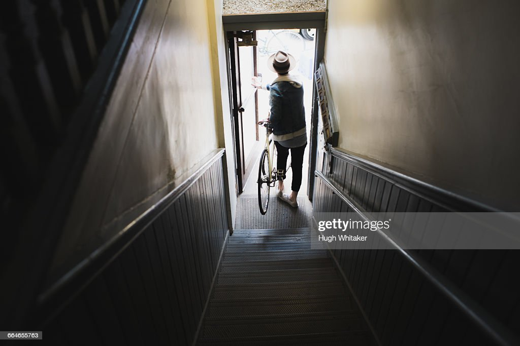Young man at bottom of stairs, exiting building with bike, elevated view : Photo