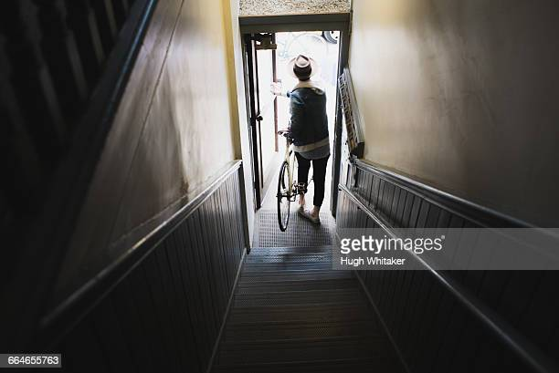 young man at bottom of stairs, exiting building with bike, elevated view - leaving fotografías e imágenes de stock