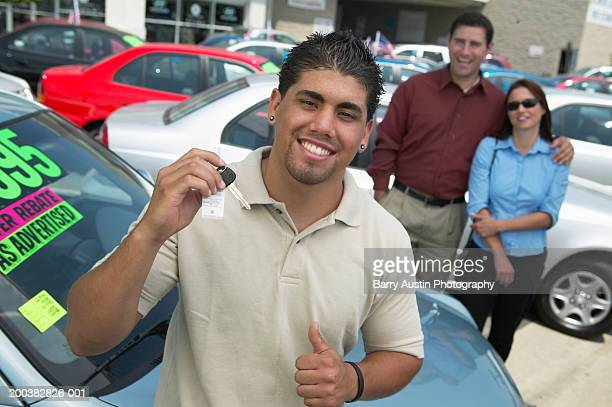 Young man at car lot, holding keys, parents in background, portrait