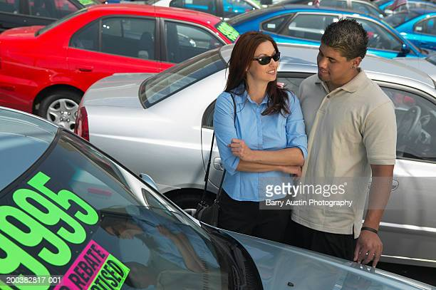 Young man at car lot, looking at car with mother, outdoors
