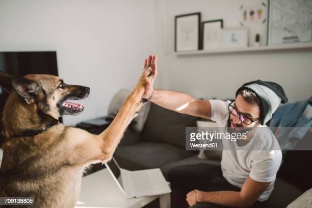 Young man at home giving high five with his dog